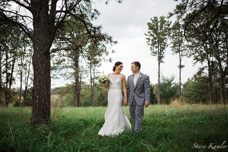 Laughing at Pioneers Park with her groom in a lace dress