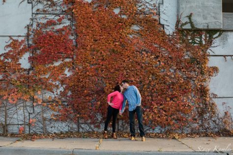 Engagement photos by fall leaves on a wall