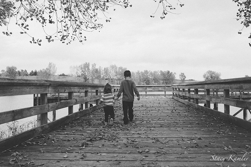 Brother and Sister walking on pier at lake
