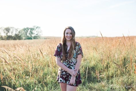 Senior in golden hour light in tall grass