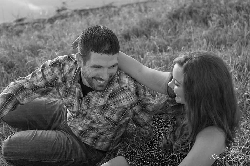 Engaged couple laughing in grass