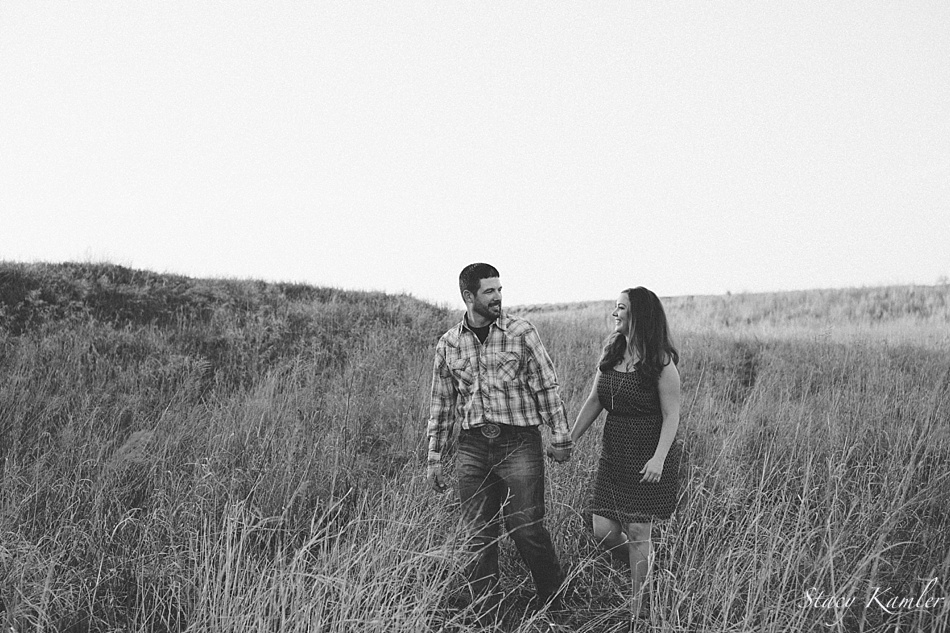 Couple walking through tall grass during engagement session