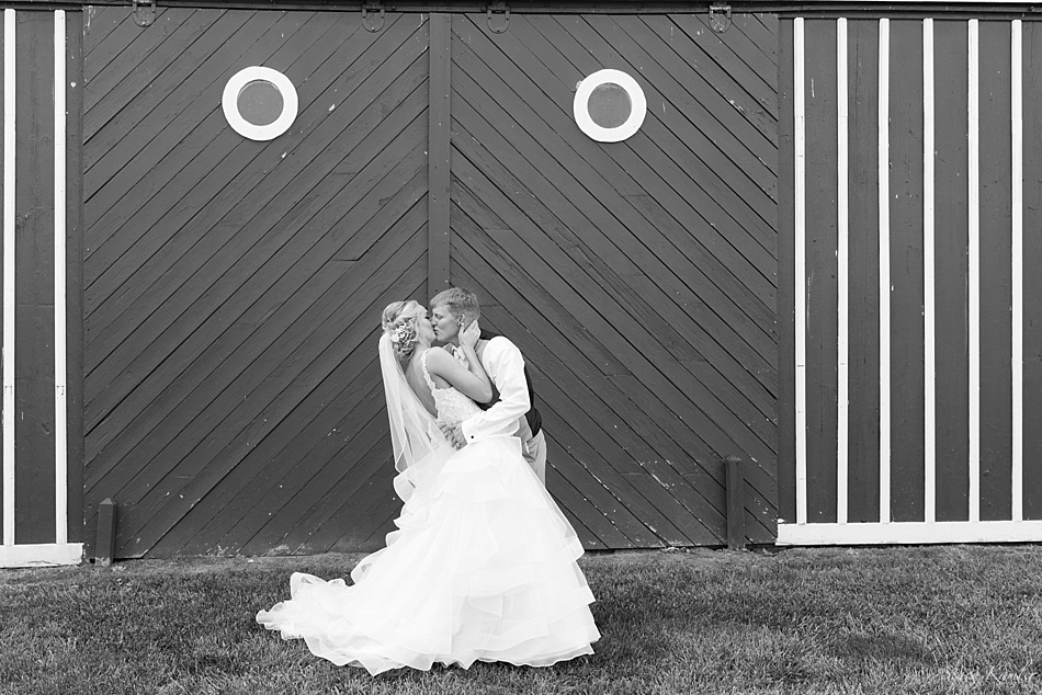 Bride and groom kissing in front of barn at Scout Rest Ranch