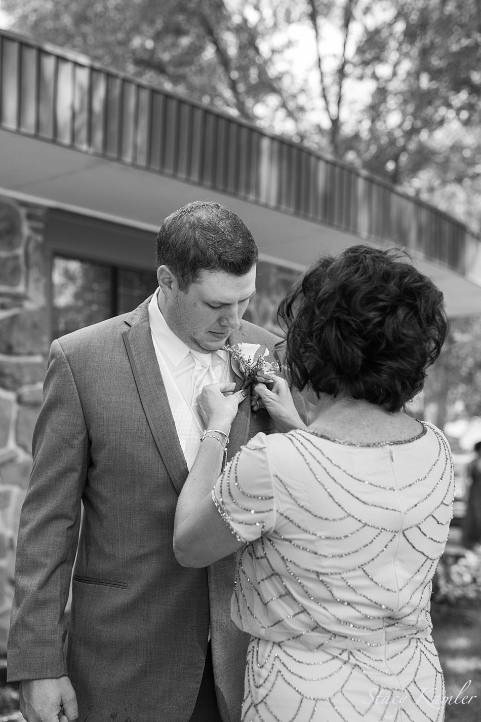 Groom and mother pinning on flower