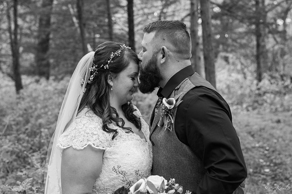 Groom kisses forehead of Bride in portraits