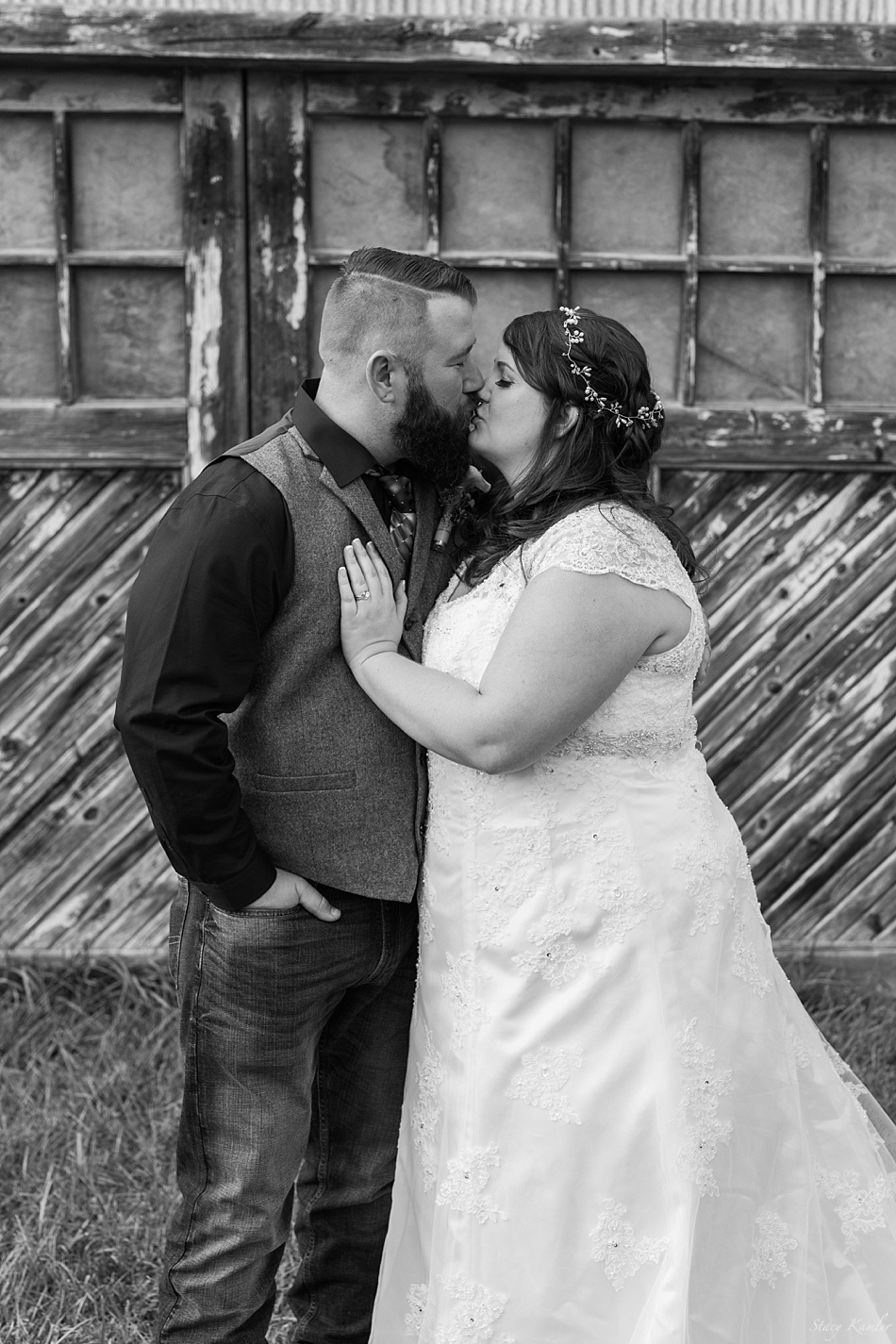 Bride and Groom kissing in front of Loma barn
