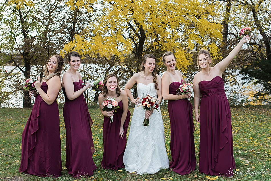 Bridesmaids posing in the fall with red flowers