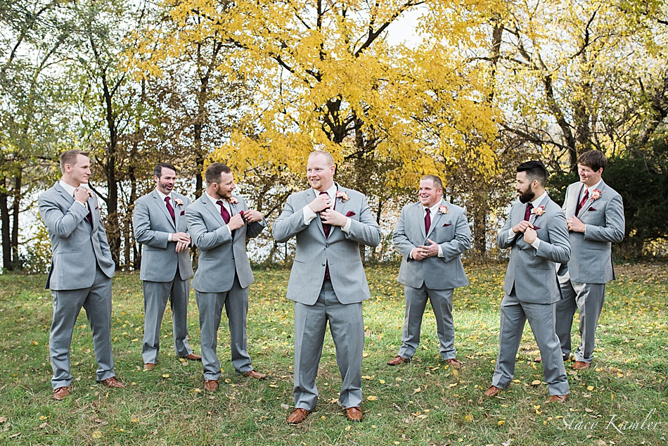 Groomsmen laughing in their grey tuxes