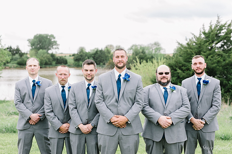Groomsmen in grey tuxes and blue vest