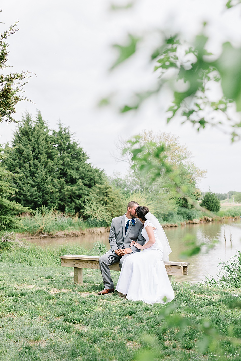 Bride and Groom sitting on bench by lake for wedding day portraits