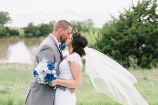 Bride and Groom kissing with veil blowing in wind