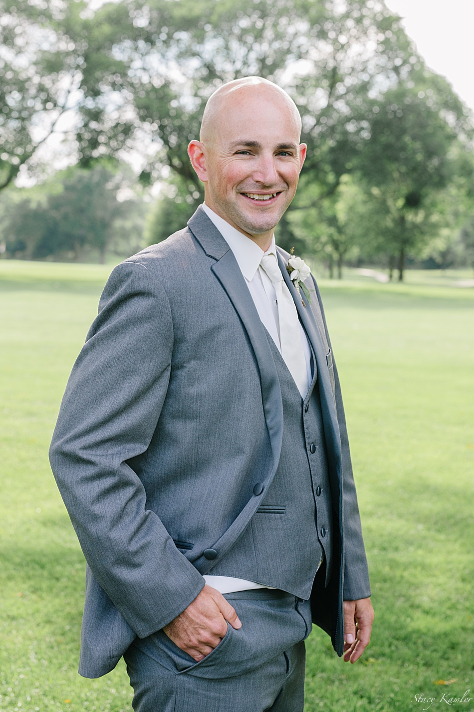 Groom wearing a grey tux and an ivory boutonniere