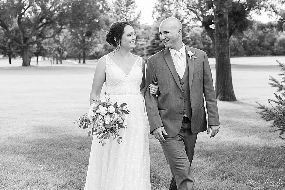 Bride and Groom walking on the golf course, laughing