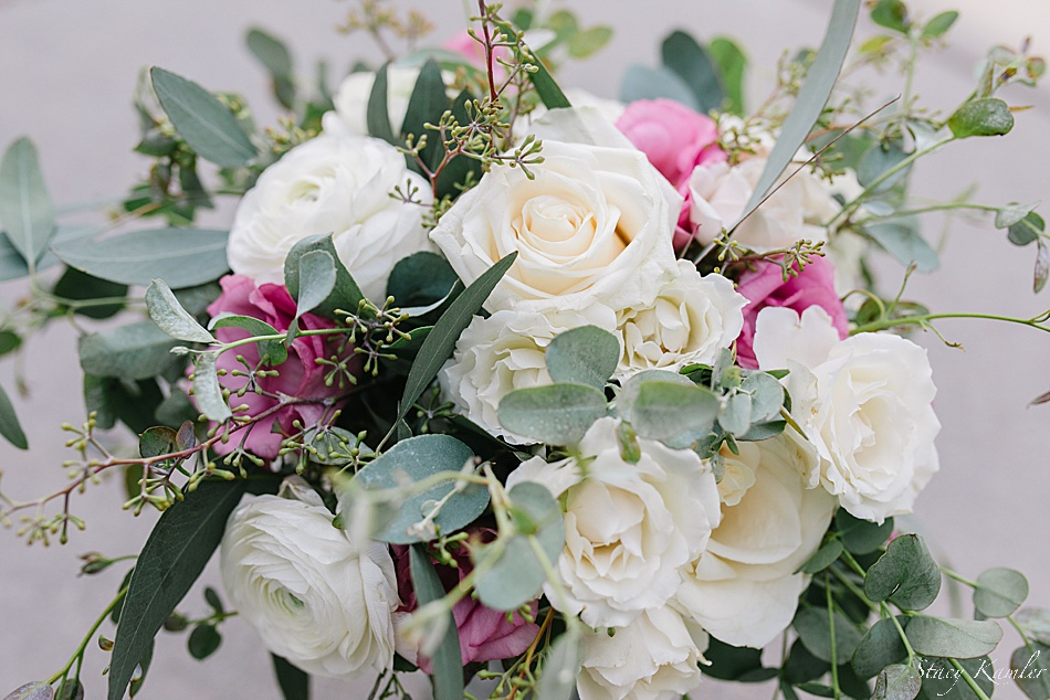 Pink and Ivory flowers and greenery in brides bouquet