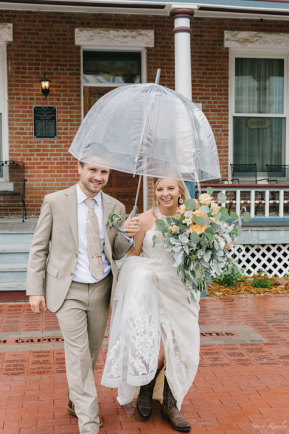 Bride and Groom using a clear umbrella in the rain