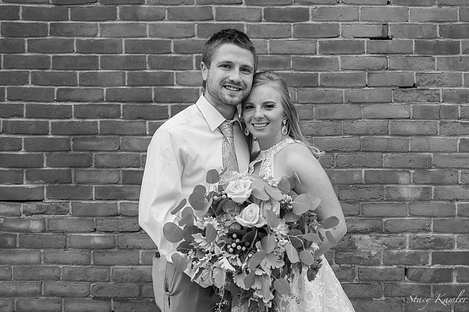 bride and groom portraits in front of brick wall