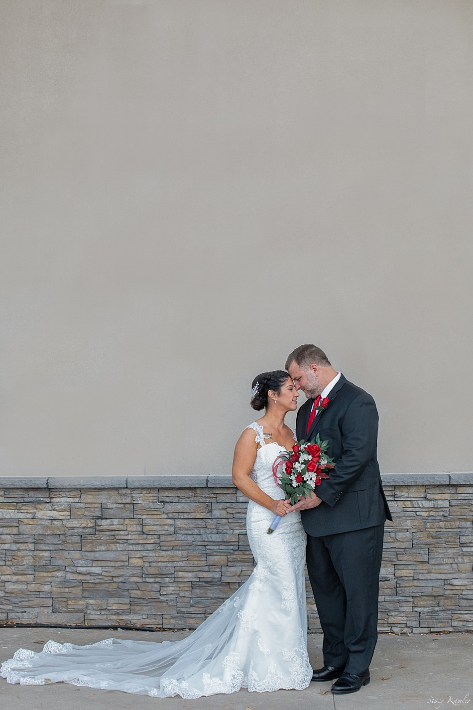 Full length photos of bride and groom and red and white flowers